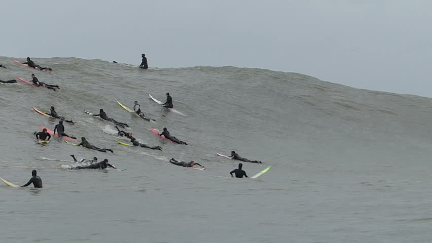 Half Moon Bay, California, USA - Dec. 20, 2014: Big wave surfers ride a giant wave at Mavericks surf break.
