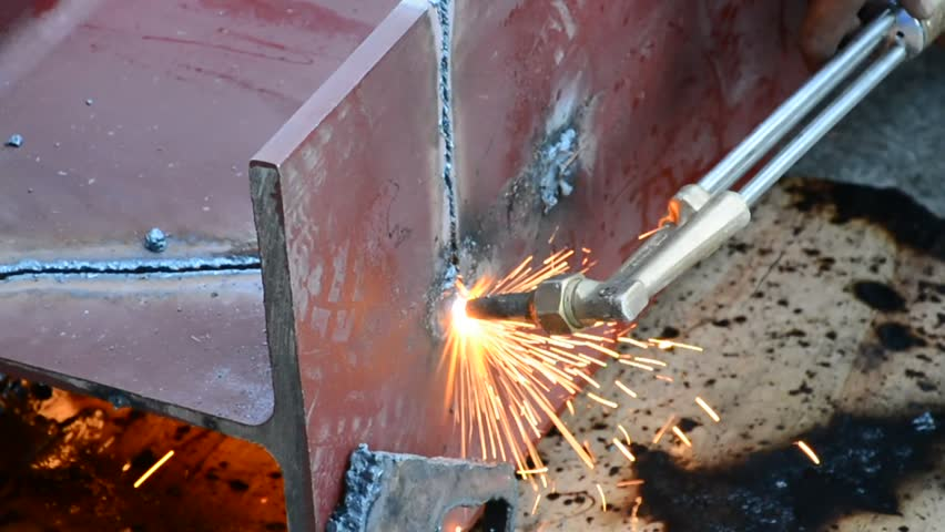 Metal Cutting With Acetylene Gas. Workman is working with torch to cut the iron in factory. Spark splash around the ground. - HD stock video clip