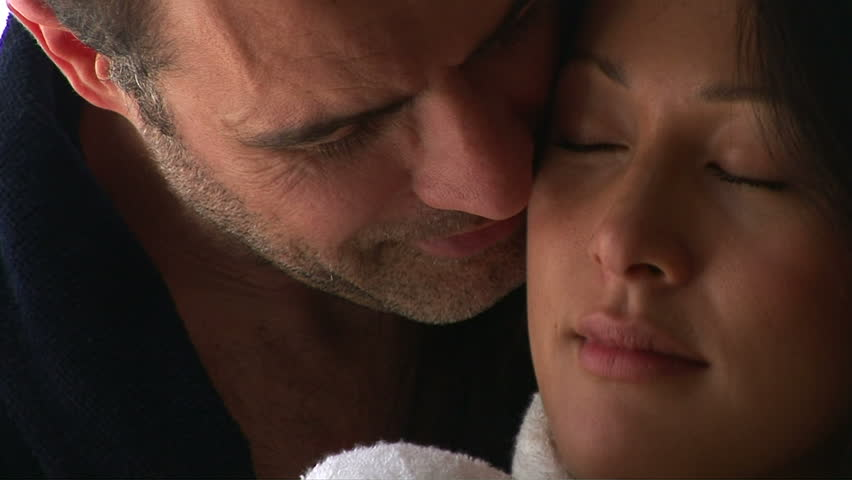 Close up portrait of young couple in bathrobes kissing - HD stock footage clip