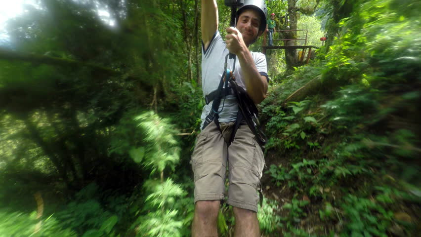 Adult men riding a zip line, cable mounted camera, model released 4k footage with audio - 4K stock video clip