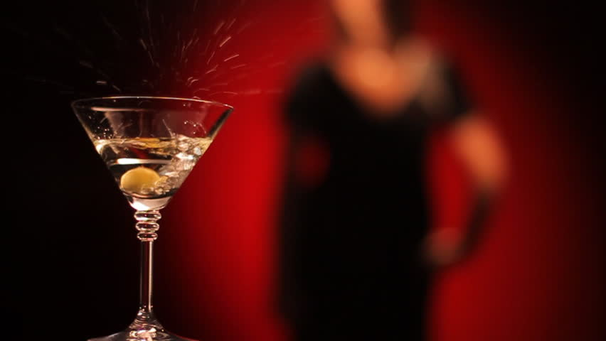 Olive falls in a glass of martini. Female silhouette on a red background - HD stock video clip
