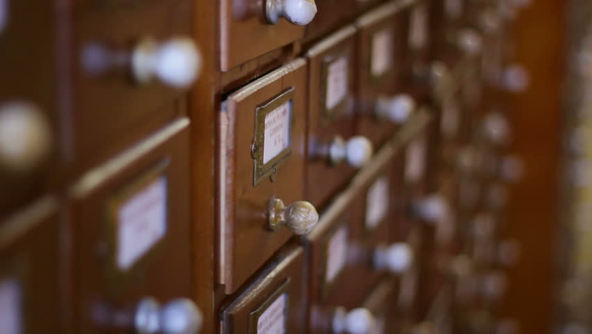 A hand open the wooden locker with database cards, for searching the right title, in a old-fashioned library, the non digitized archive.