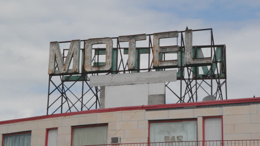 Motel sign. Big sign on top of cheap motel. Pigeons landing.