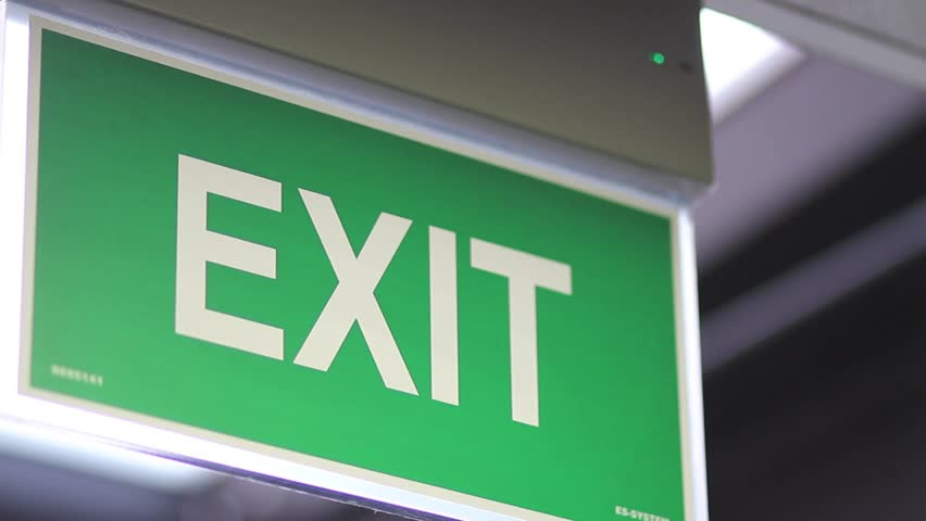 A close up shot of an emergency exit sign which goes into focus and goes out of focus/We have to go out
