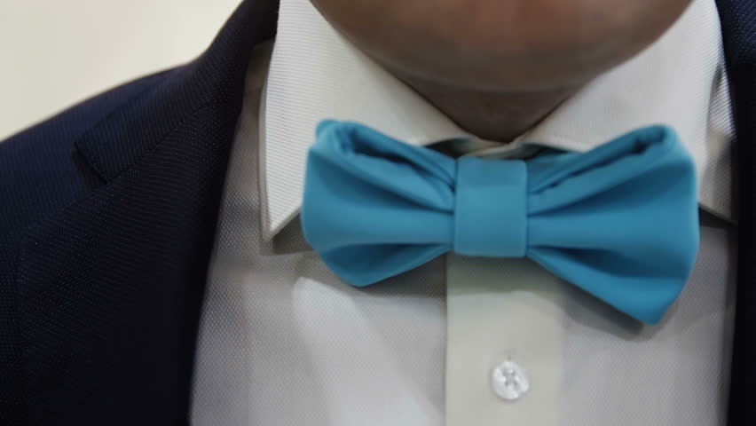 the man adjusts his bow tie close up wedding