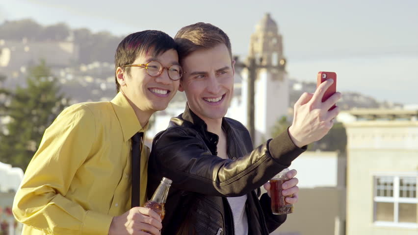 Happy Gay Couple Take A Photo Together On A Rooftop With City View