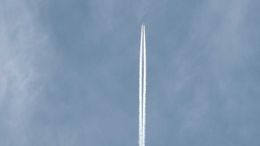 Airplane flies overhead through frame on lightly cloudy blue sky day leaving behind vapor trail jet contrails. - 4K stock footage clip