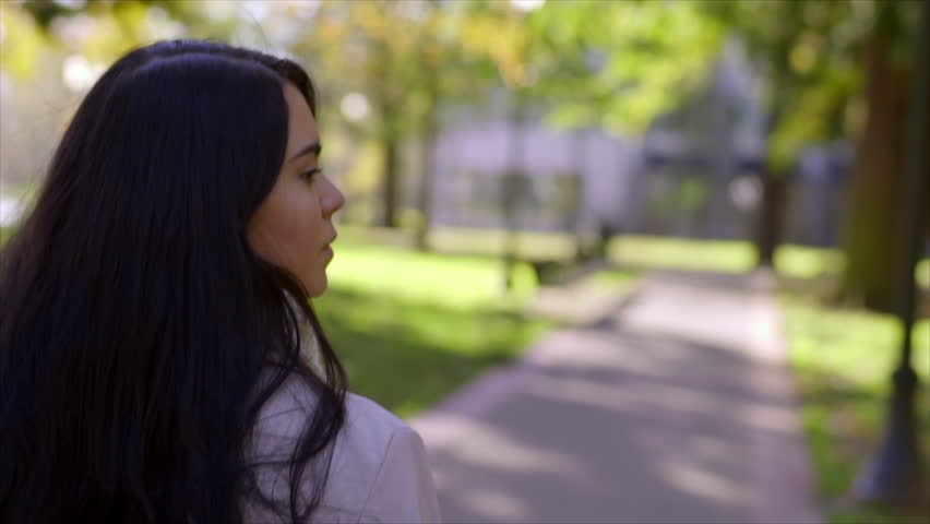 Camera Follows Behind Teen Girl Walking Through City Park, She Looks Around, Daydreaming