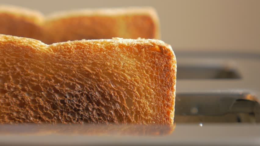 Roasted toast bread popping up from toaster machine while smoke comes out 4K 2160p UHD footage - Two toast pieces popping out from toaster 4K 3840X2160 UHD video