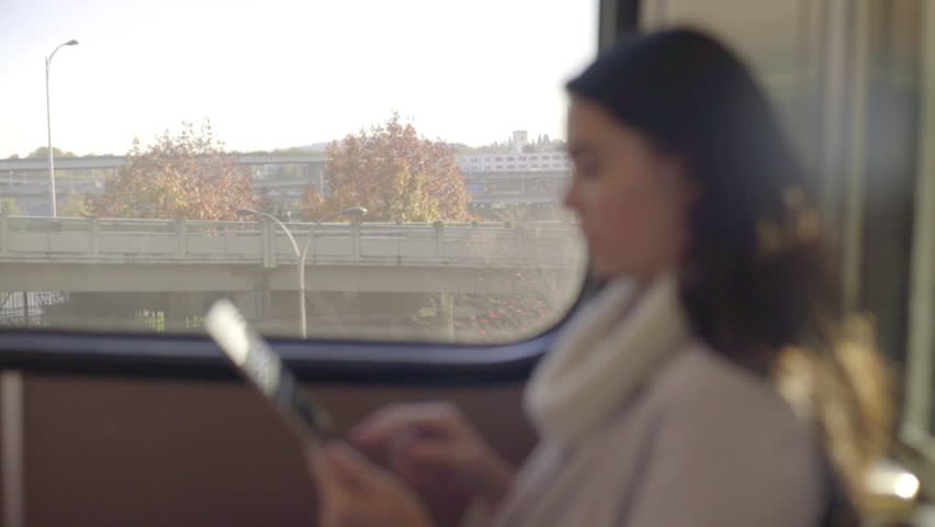 Close Up Of Happy Mixed Race Young Woman Using Her Tablet On A Train