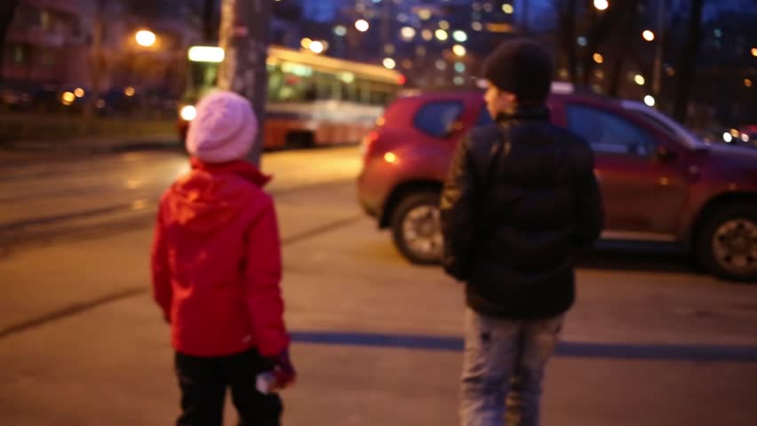Back of boy and girl hold hands and walk on street near road with tram at evening