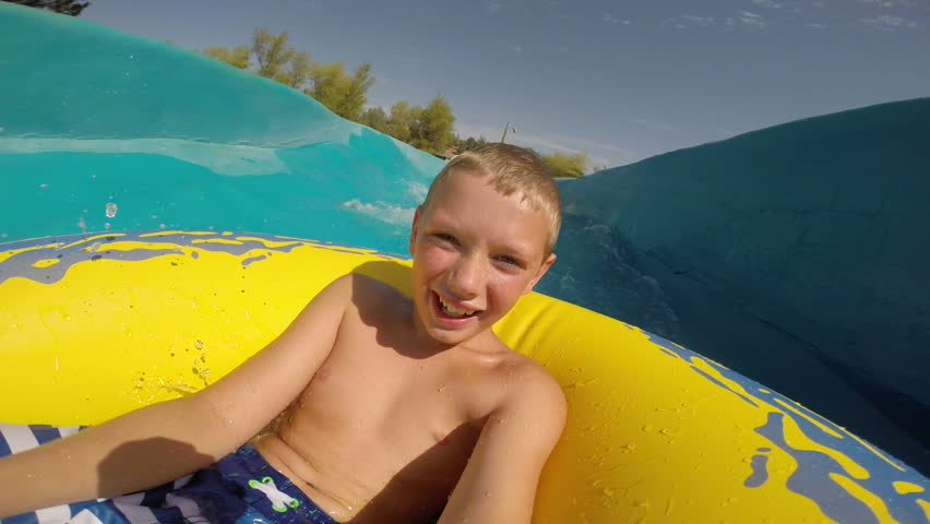 Young boy going down a waterslide at waterpark, POV video