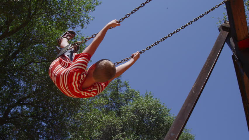 Young boy swinging at park in slow motion