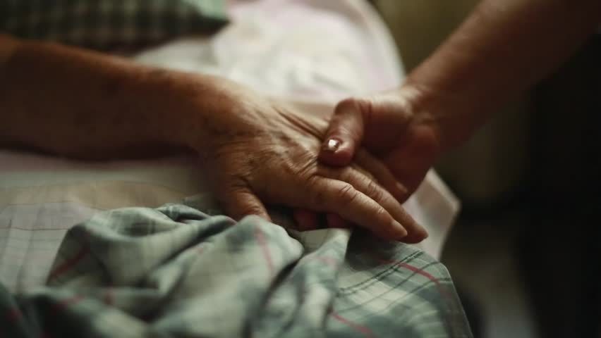 Pan of Unrecognizable Elderly person holding hands with another person to the bed where she is lying down