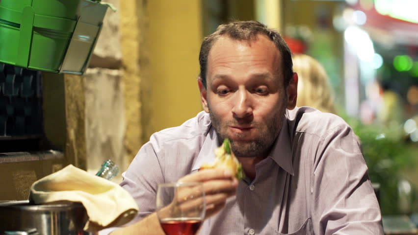 Portrait of young, funny man eating sandwich in cafe at night