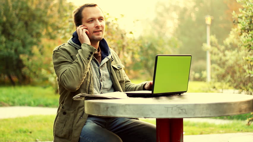 Man working on laptop in the park and talking on cellphone  - HD stock footage clip