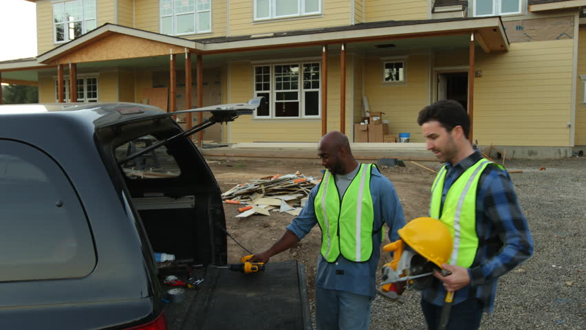 Construction workers load truck with tools