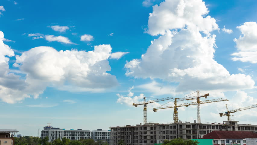 4K video time lapse : Construction site with cranes and blue sky background with downward movement.