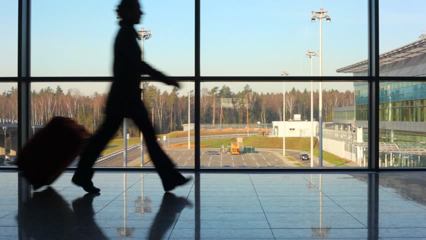 silhouettes of family hurry to aircraft against window at airport - HD stock footage clip