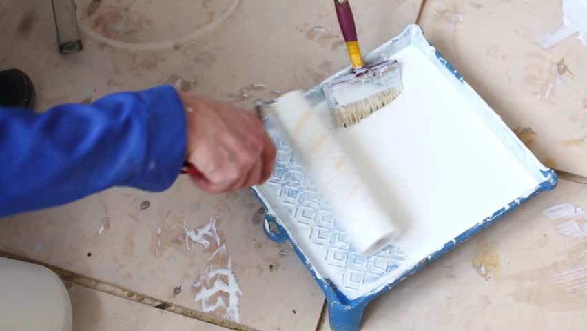 Worker dunks roller into the tray with the glue on the floor - HD stock footage clip