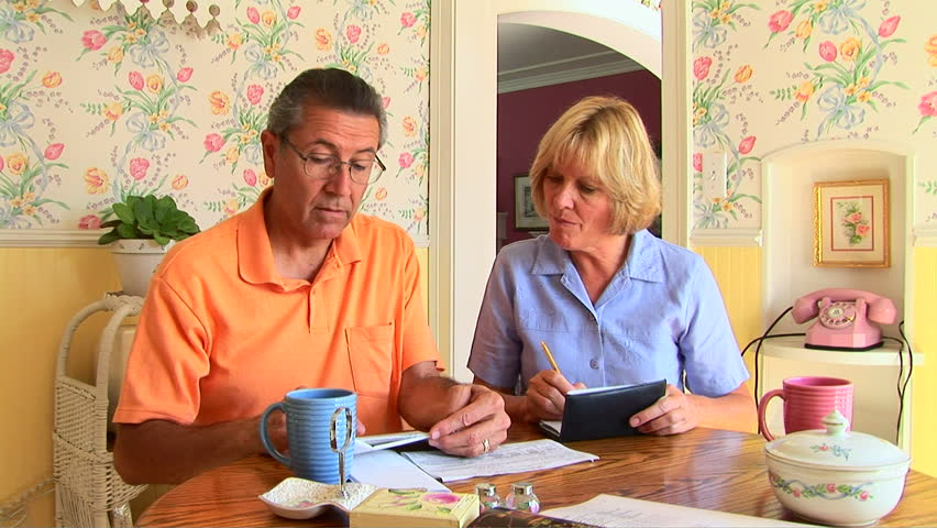 Mature couple going over bills at table - HD stock video clip