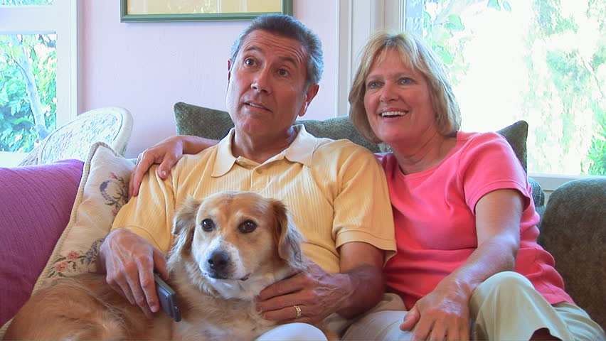 Portrait of mature couple watching television with dog - HD stock video clip