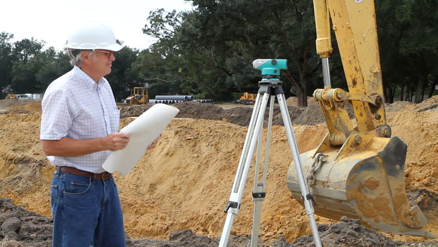Civil engineer reads architectural blueprints and inspects the work at a construction site. - HD stock footage clip