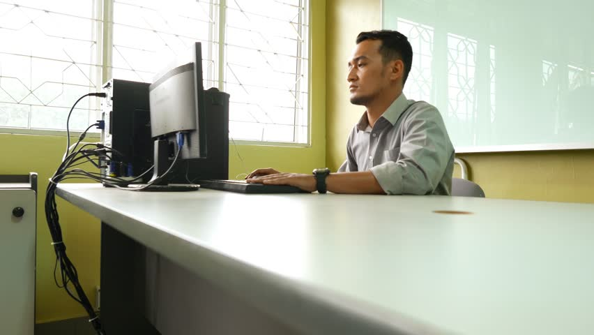 A serious male employee using a computer and surfing the internet, dolly shot