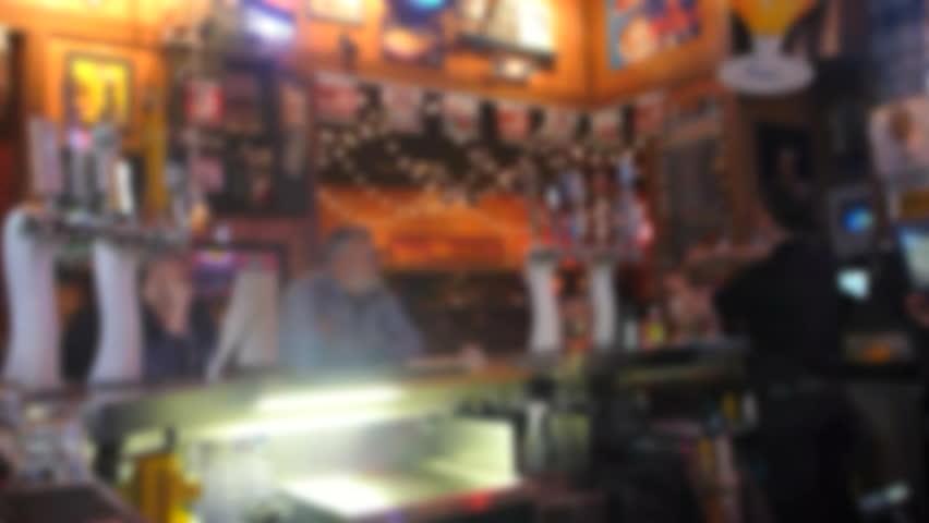Soft focus, unrecognizable people at sports bar, time lapse.