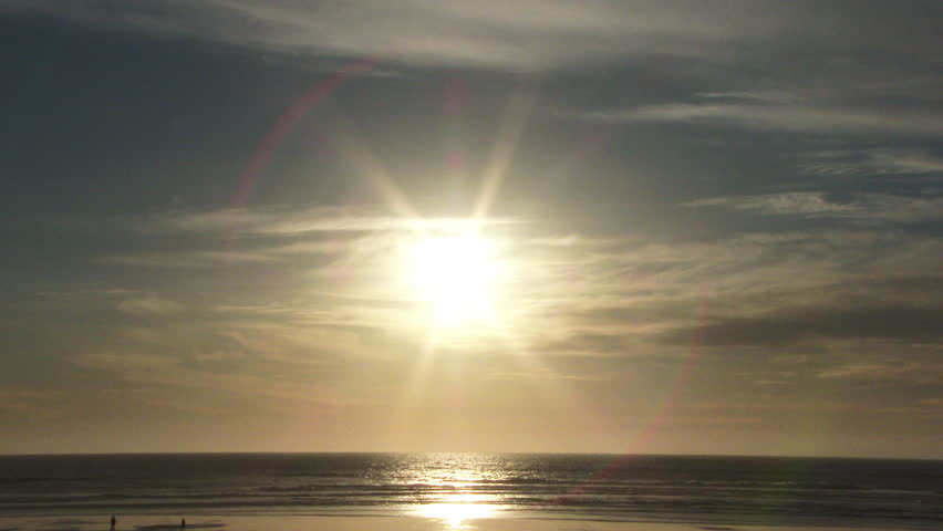 Sun shining down on sandy beach in the Pacific Northwest, Oregon near sunset, wide angle.