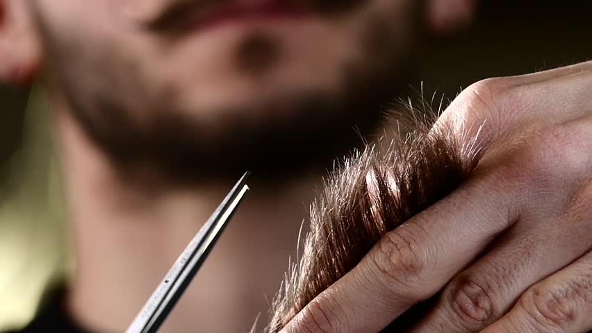 Male hand cut their hair. Lifted her hair and starts work with scissors. Action takes place in the barber shop. Slow motion