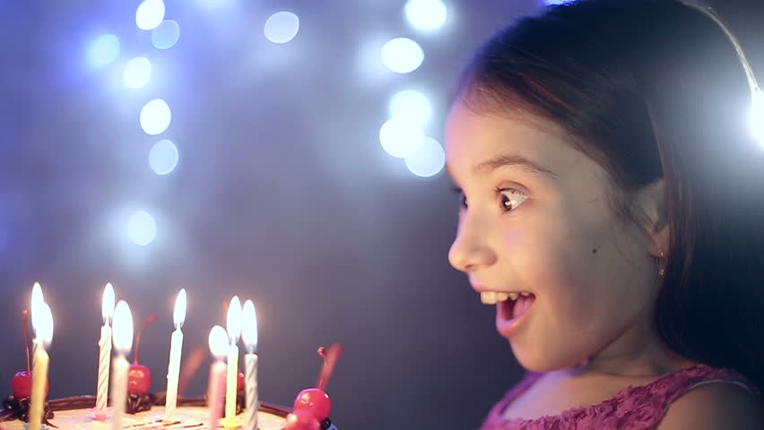 Birthday of the little girl she blows out candles on cake. Slow motion