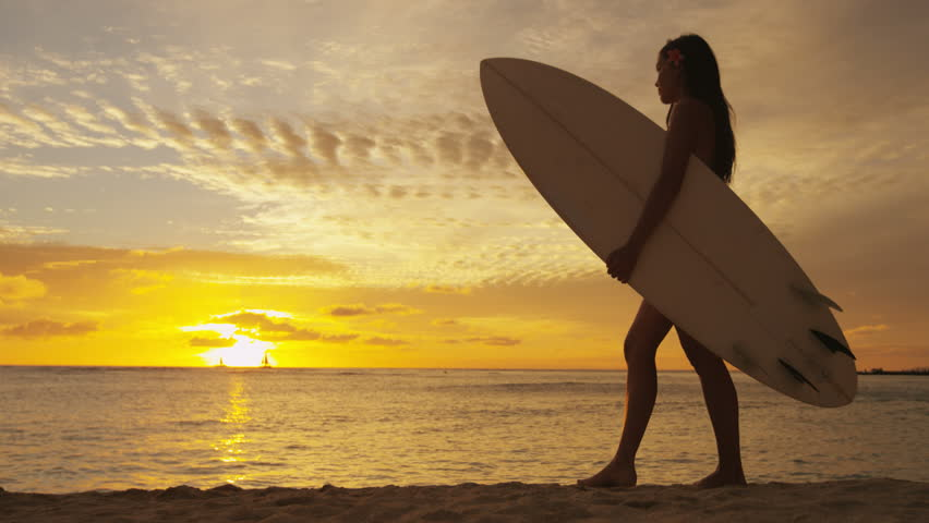 Surfer woman in silhouette walking with surfboard at sunset on tropical beach. Surfing girl looking at ocean sunset. Female bikini woman by water standing with surfboard in healthy active lifestyle. - 4K stock video clip