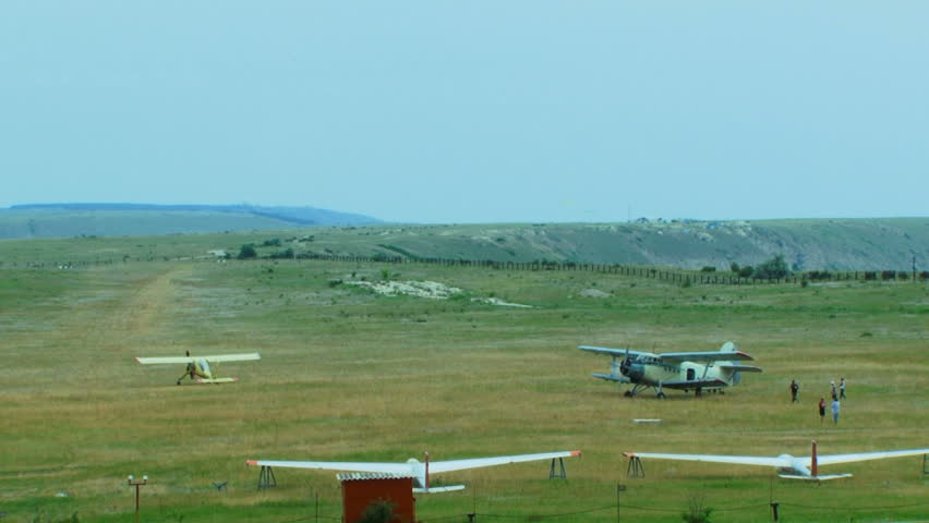Panoramic shot of the airfield with just landed small airplane called crop duster with moving and propeller  and with another small airplane in a distance and two sailplanes on the foreground. Airfield