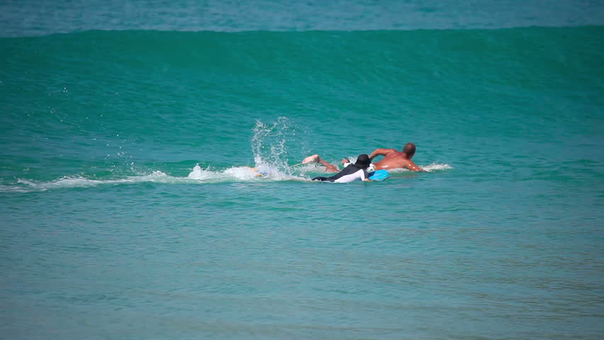 NAI HARN BEACH, PHUKET, THAILAND: NOVEMBER 28, 2011- A surfers catches a wave at Nai Harn beach. Multiple surfers in the ocean waiting for waves. - HD stock video clip