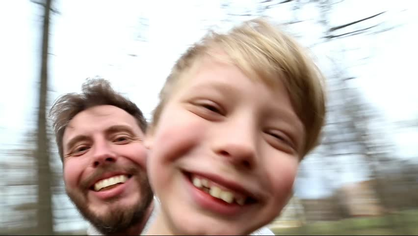 Father and son spinning around together while taking selfie in park. Point-of-view shot Family have fun outside. Happy dad and kid looking at camera. Smiling and laughing man and child. Spring park