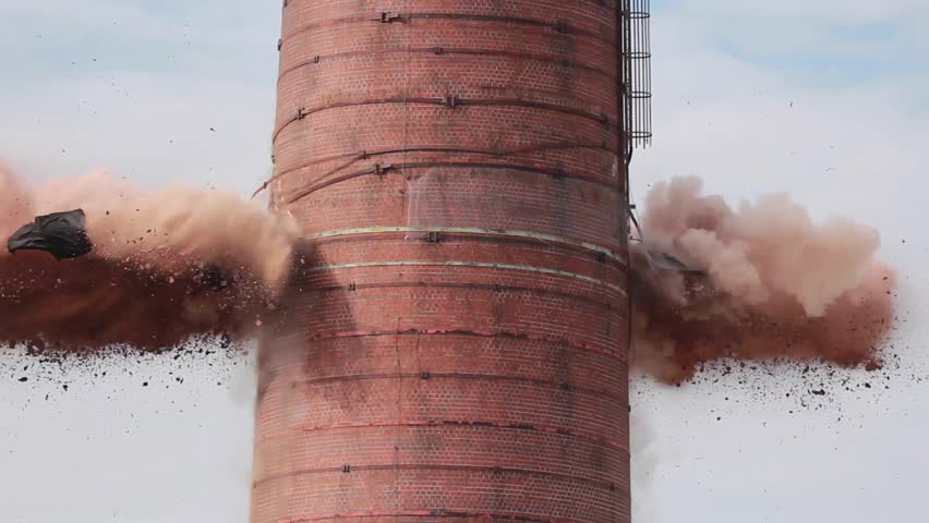 Explosion as smoke stack implodes and crumbles