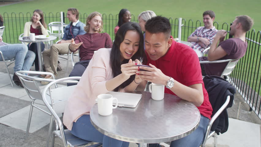 4K Happy attractive young couple, posing to take their own picture at outdoor cafe