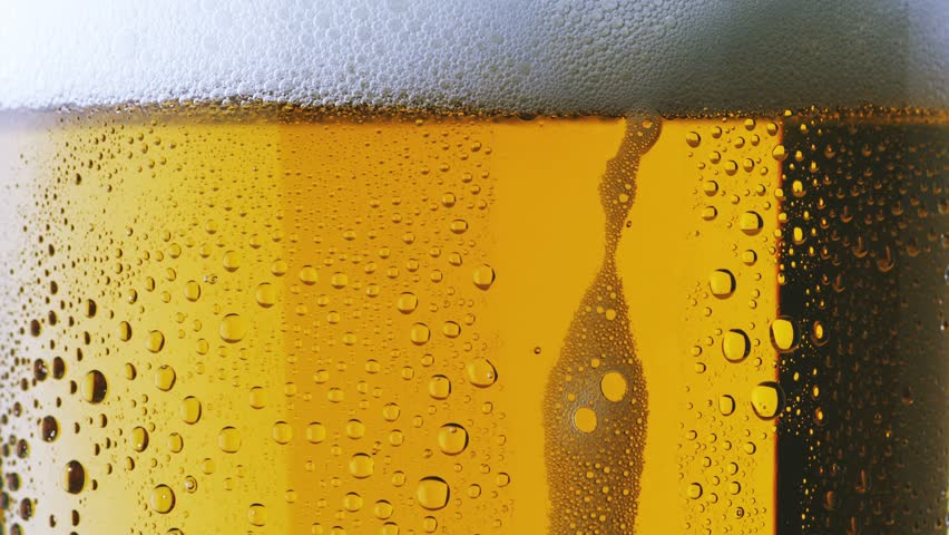 Foam sliding down side of beer glass - HD stock footage clip