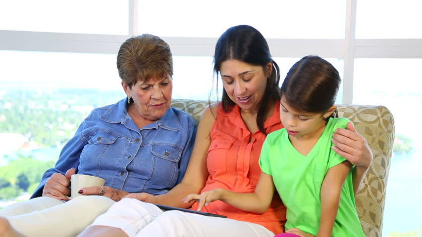 Tilt down to reveal latina hispanic mother and grandmother having a conversation then joined by granddaughter to show them her tablet.