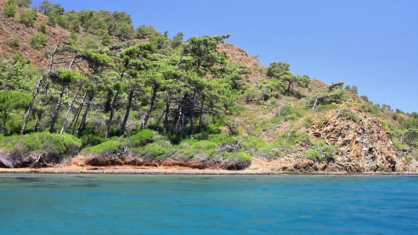 Blue voyage cruise in Turkey. Sailing along Bodrum, Marmaris, Datca, Fethiye shores. Wild and beautiful Mediterranean Sea with pine trees on the coast.