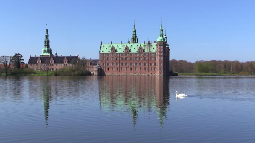 Swan swimming in front of Frederiksborg Castle in Hilleroed, Denmark, on a sunny spring day. The castle is built in Dutch Renaissance style and is located on three islands in the castle lake.  - HD stock video clip