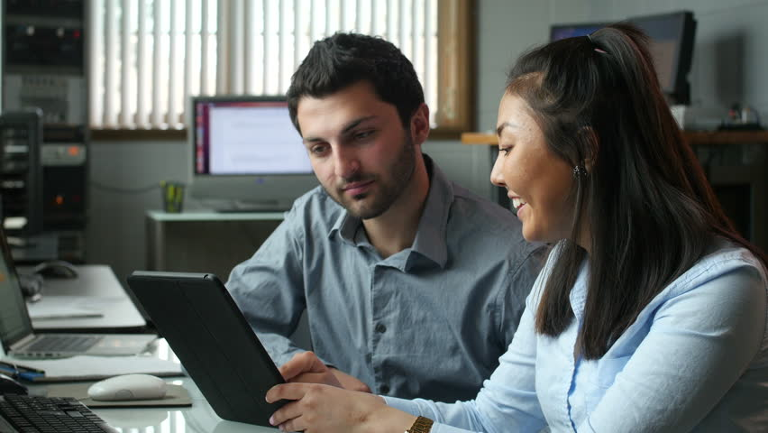 Young professionals working together on tablet in the office