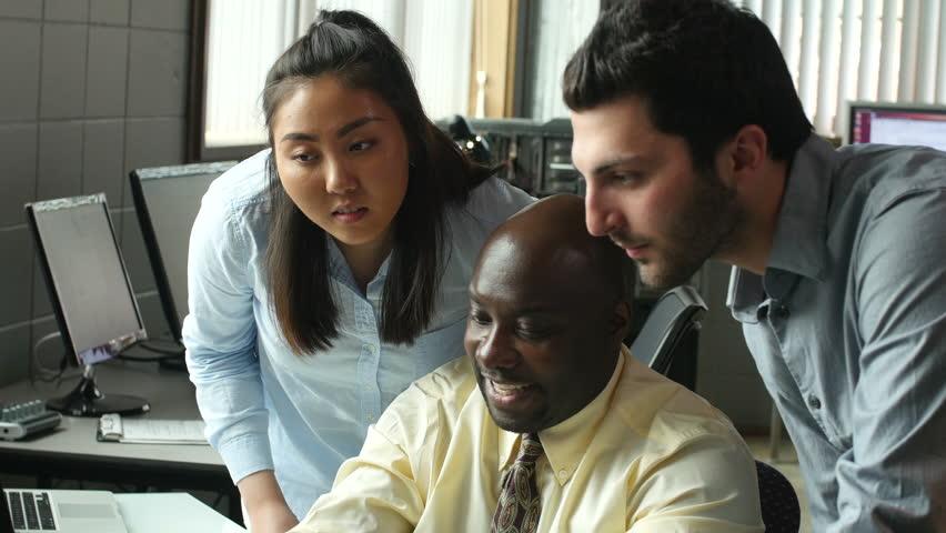 Diverse Business Professionals celebrating at desk