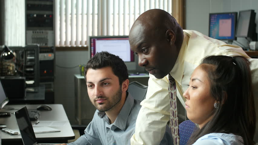 Diverse business professionals in modern office at computer