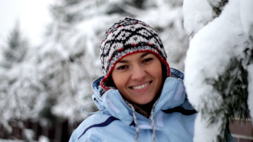 Smiling winter woman standing under pine tree with snow falling on her  - HD stock video clip