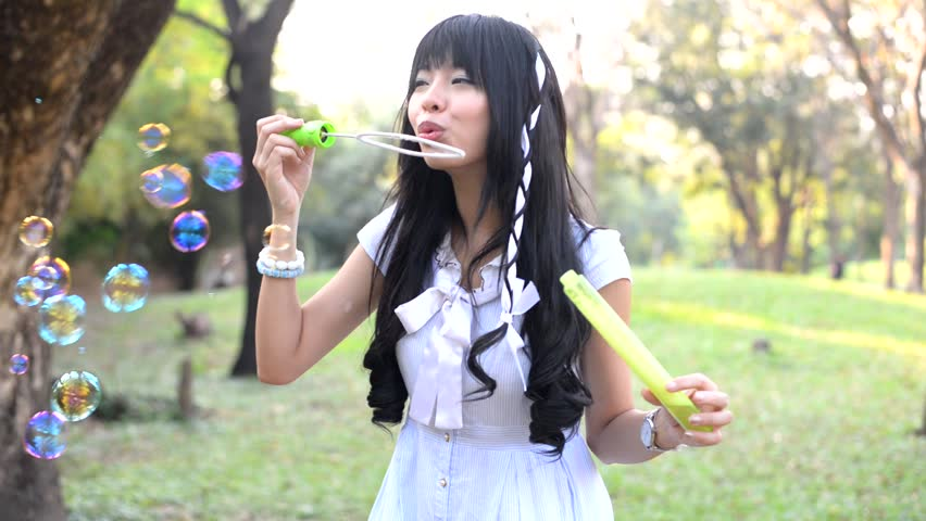 Little girl diligently blowing soap bubbles in the forest for Tiny thai teen