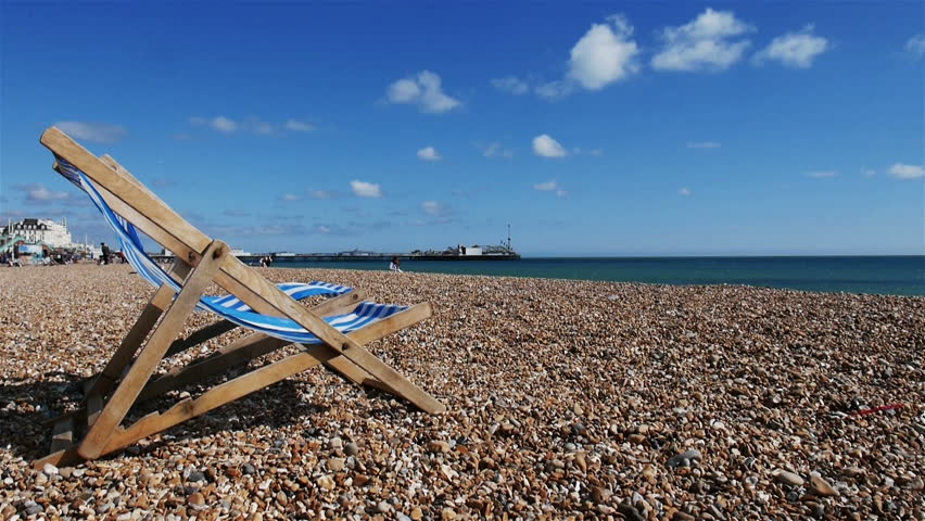 Wide angle HD video footage of a traditional seaside deckchair blowing in the wind on a bright spring day on Brighton beach in the south coast of England.  Brighton Pier is visible in the distance. - HD stock video clip