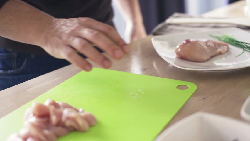 Man putting chicken breast on chopping board in kitchen, slow motion shot at 240fps