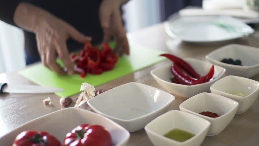 Man putting chopped red pepper into bowl in kitchen, slow motion shot at 240fps